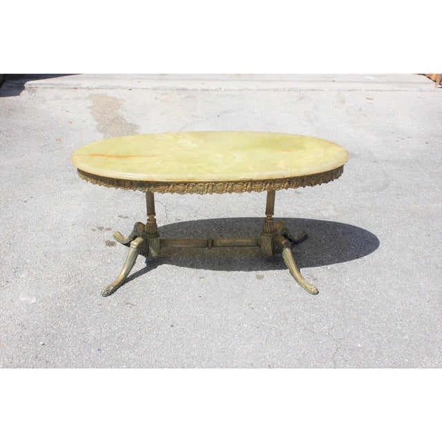 Classic French Maison Jansen oval coffee or cocktail bronze table with green onyx top. Made in the 1940s. The onyx are in...
