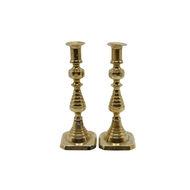 A pair of gold brass candlesticks. Central columns are turned with hive like bulbs and stand on square bases. Patina...