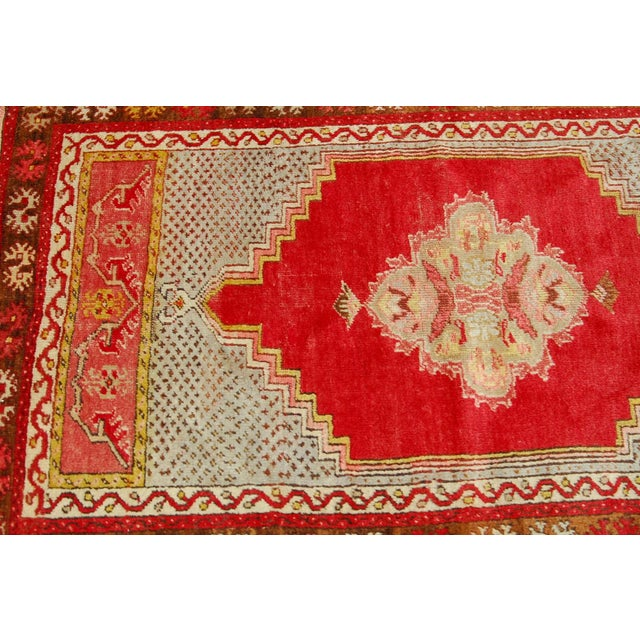 Chic prayer rug with classic design and vibrant colors of yellow, pinks, brown, and grey over red. Made with vegetable...