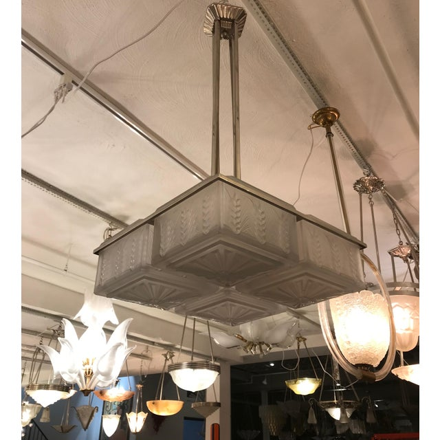 """French Art Deco chandelier signed by the French artist """"Hettier Vincent"""". Having four square shades enhanced by geometric..."""