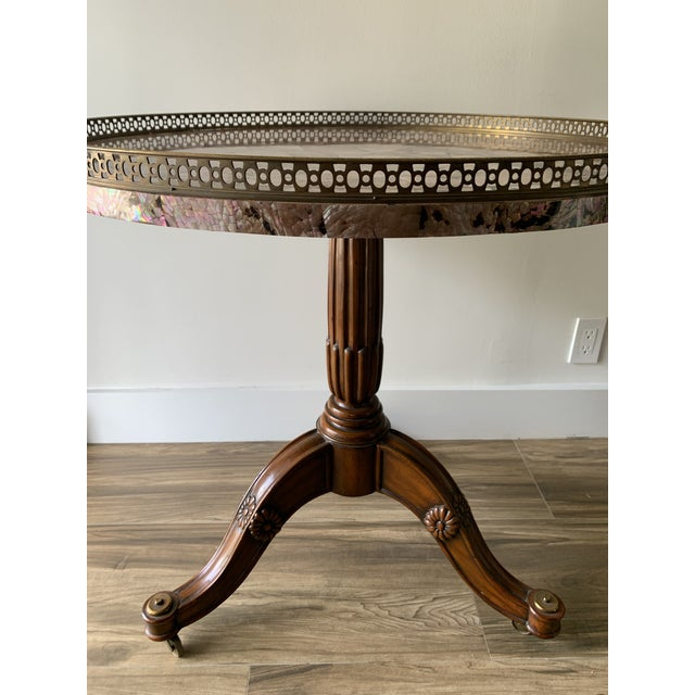 Impressive, elegant, round occasional or side table by Maitland Smith. Inlaid abalone shell top with brass inner circle...