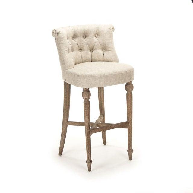 Curved tufted back bar stool upholstered in cream natural linen on limed grey oak frame.