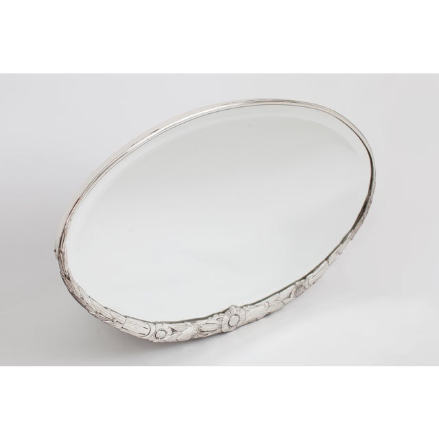 A delicate oval art deco mirror with finely-incised floral and foliate décor of wheat shafts and poppies, in beautifully...