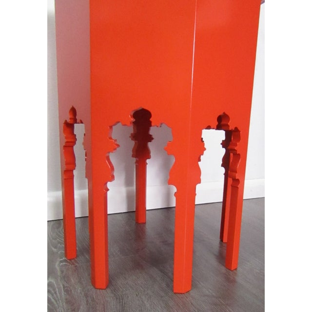 Round table with Moroccan cut out designs on the sides forming legs. The table has been refinished in a bold orange...