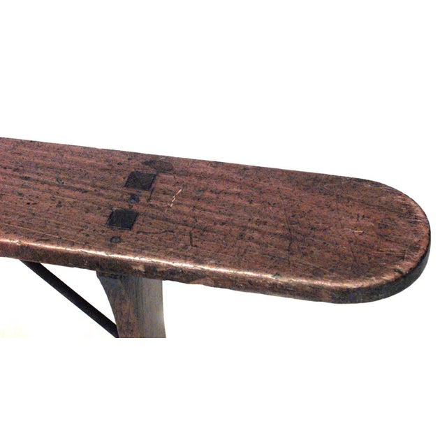 Rustic Italian Renaissance style fruitwood bench with solid spreading trestle legs with iron supports (19th century).