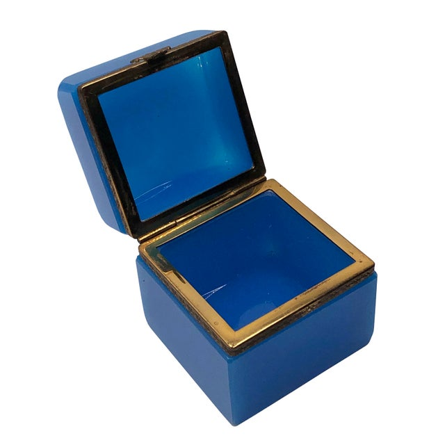 A vintage blue opaline with gold trim trinket box with a hinged top. From France, 1940s.