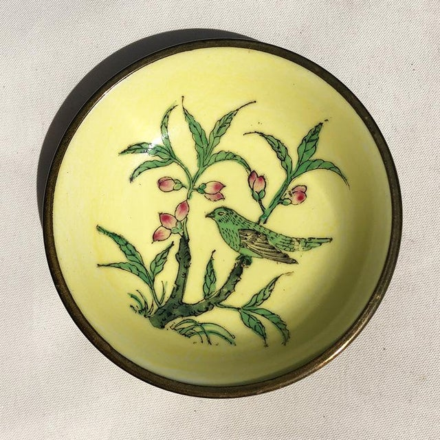 Yellow round Chinese dish with green bird and pink lotus flowers and leaves. The bottom of the piece is covered in a brass...