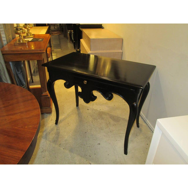 A whimsical Hollywood Regency ebonized table on splayed legs with central drawers.