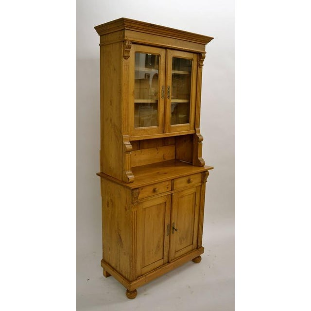 This is an unusually small Dutch pine buffet, built in two pieces. Beneath a replaced crown moulding are two glazed doors,...