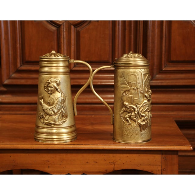Decorate your bar with this pair of antique brass beer mugs; crafted in Belgium circa 1880, the pitchers with handles and...