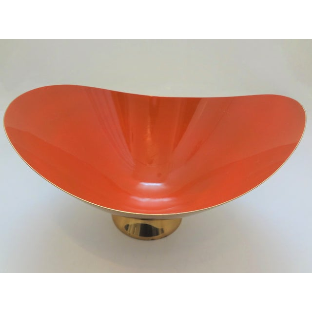 A classic mid century modern bowl by Donald Colflesh for Gorham. An abstract form with a bright brass exterior and orange...