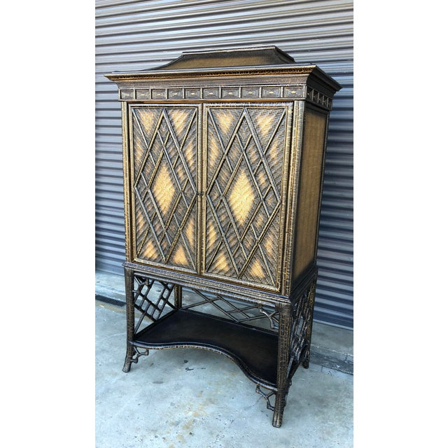 Chinoiserie pagoda style rattan cabinet/armoire. Black crackle finish over rattan. Chinese chippendale fretwork details....