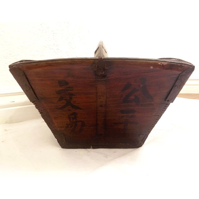 A rustic antique Chinese rice measure basket with beautiful patina, original metal hardware and old black Chinese...