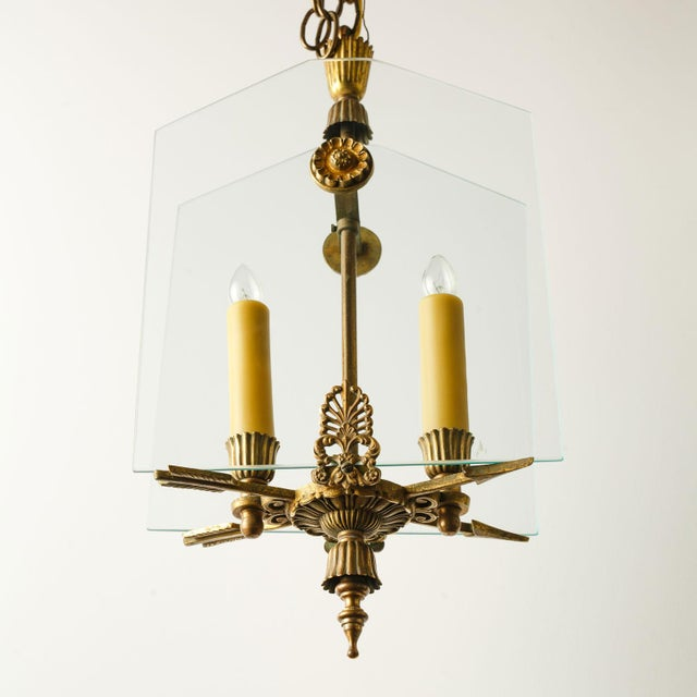 French classic brass and glass lantern. Two candelabra-size lights partially enclosed by two plates of clear glass. A...