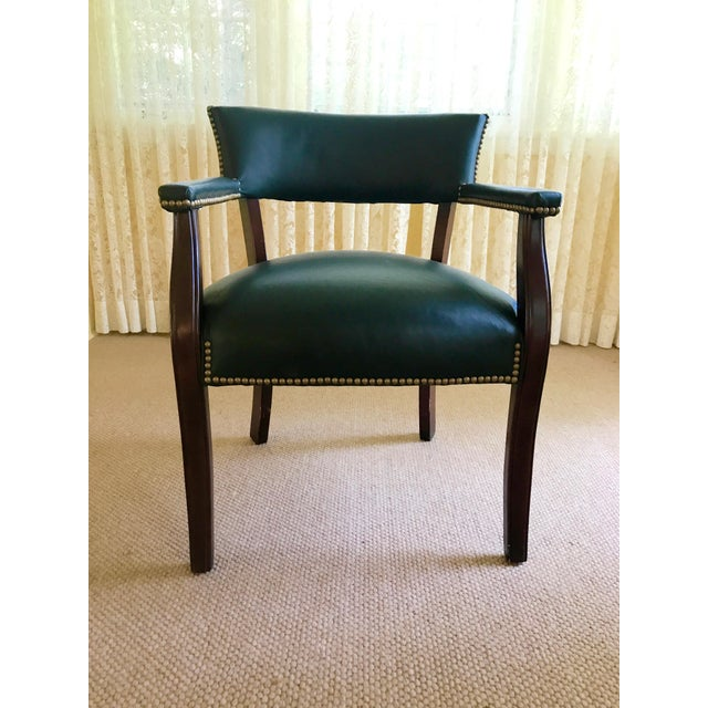 This impressive club chair is upholstered with a forest green leather affixed with nail heads. The combination of the...