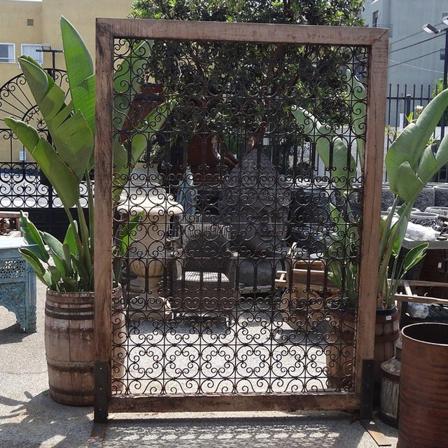 Teak frame with iron work. Used as an outdoor screen or indoor room decider.