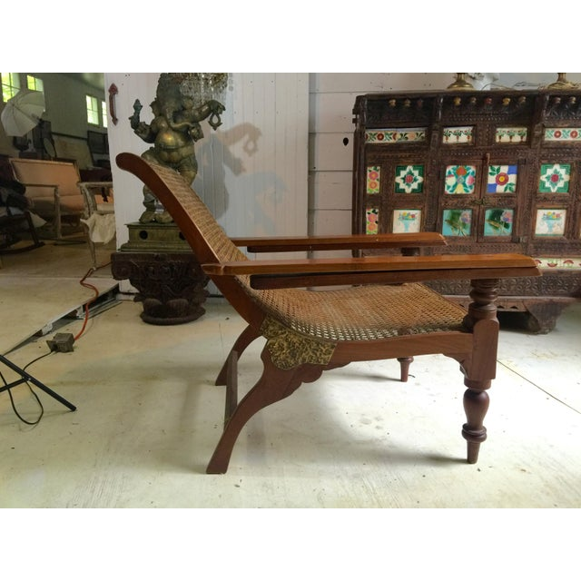 Teak and cane plantation chair with fold out arms. Originally designed to fold out arms to help in taking off bpots