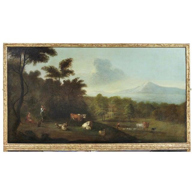 Rectangular with large pastoral landscape over mirror panels all set in a carved giltwood frame.