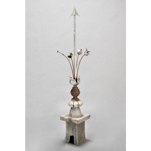 Early 20th century rooftop finial rendered in zinc with an arrow shaped center surrounded by tall stemmed flowers....