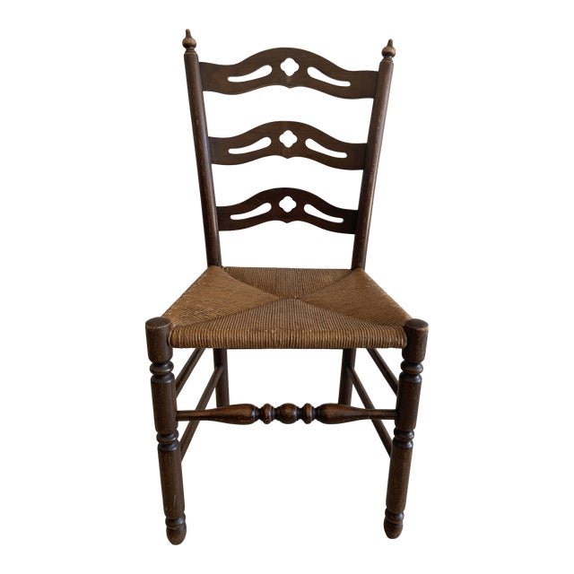 Early 20th Century French Country Carved Pierced Ladder Back Chair With Rush Seat For Sale