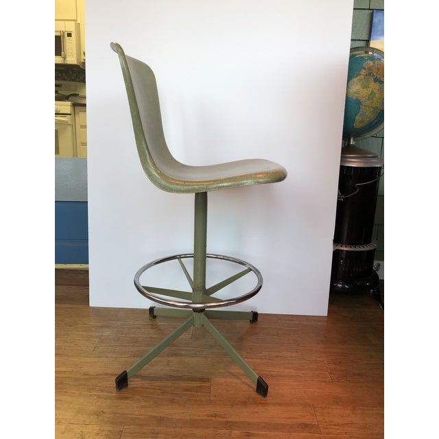 This fiberglass stool features classic mid-century design with foot rest and swivel motion. Manufactured by Hamilton Cosco.