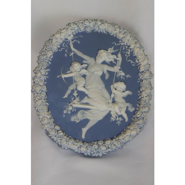 Blue and white jasperware. Lady on a swing surrounded by cupids. In the style of Wedgewood. Wire for hanging.