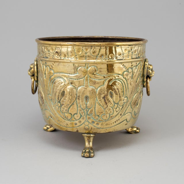 French flower pot in brass with lion motifs.