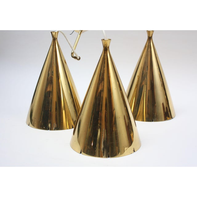 Impressive three-fixture solid brass chandelier, circa 1950s. Composed of three large brass pendants with perforations...