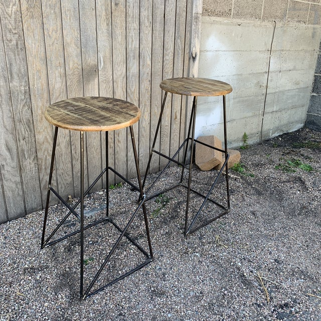 Modern Rustic bar stools from Kalalou. Distressed and stained mango wood seat over think bent metal base. There is a foot...