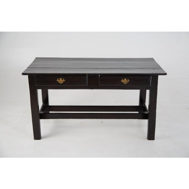 Sleek and simplistic black lacquered vintage wooden desk with brass ornate handle pulls. This desk features two pull-out...