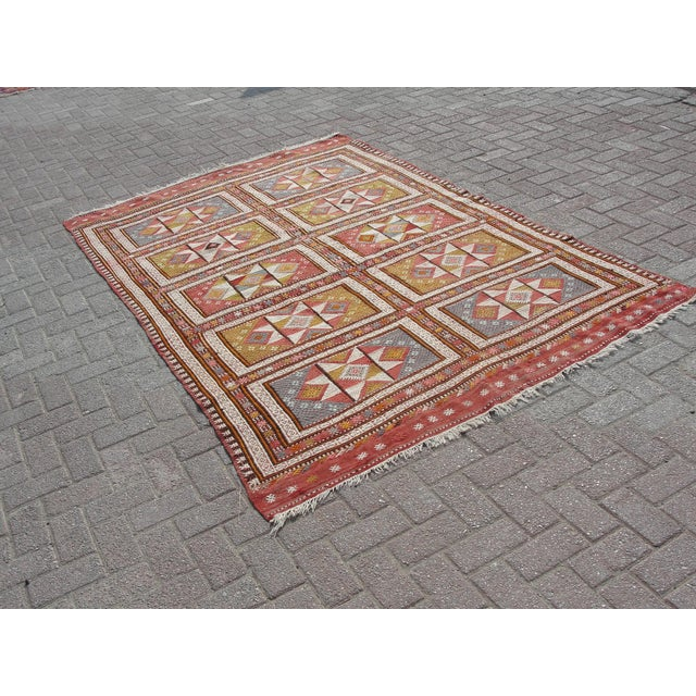 Vintage handwoven Turkish kilim rug. The kilim is nearly 65 years old. It is handmade of very fine quality natural wool in...
