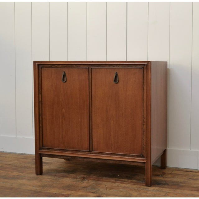 Two door cabinet by John Stuart. Walnut. Unique tear drop hardware. Smart size for storage and/Or dry bar. One shelf. *...