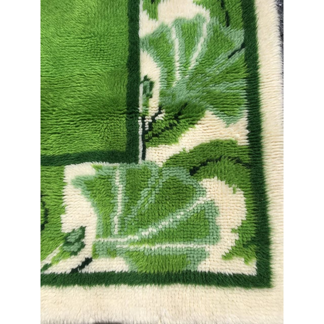 Groovy green and white wool rya rug with swirling paisley and fan designer surrounding a vibrant kelly green center panel....