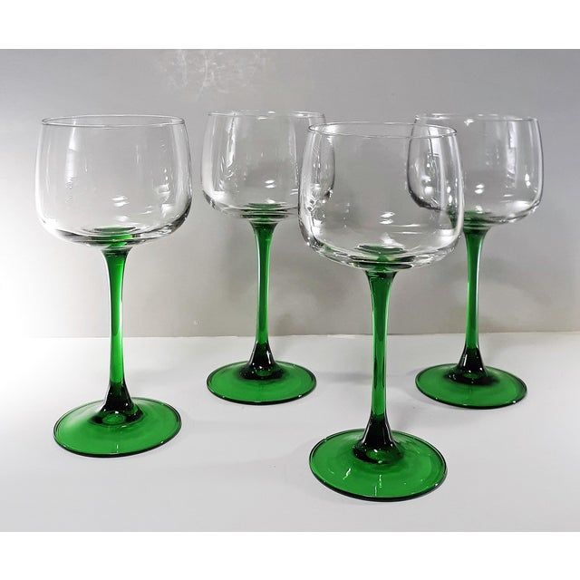 Vintage green-stemmed wine glasses made in France. Blown glass with brilliant emerald green flared stems and a clear glass...