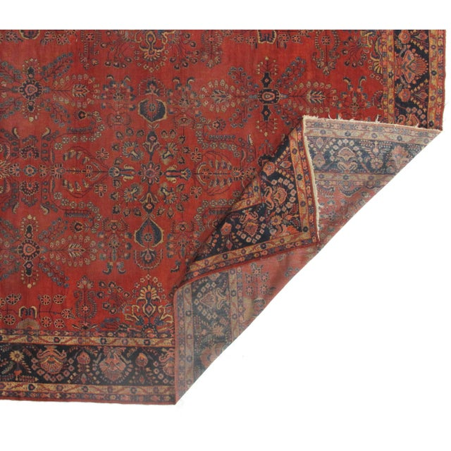 This is an antique handmade rug from the early 20th century. The piece was crafted from lamb's wool on a cotton foundation...