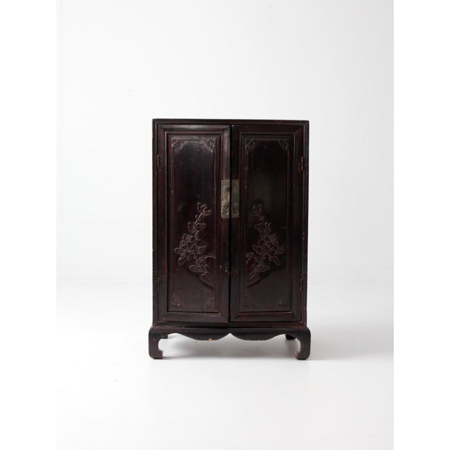 An antique Asian cabinet. The dark lacquered wood cabinet features an arched leg base and carved floral pattern. Has...