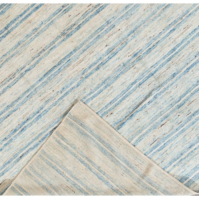 A 21st century Moroccan-style rug, hand knotted from the highest quality wool with an ivory field and light blue stripes....