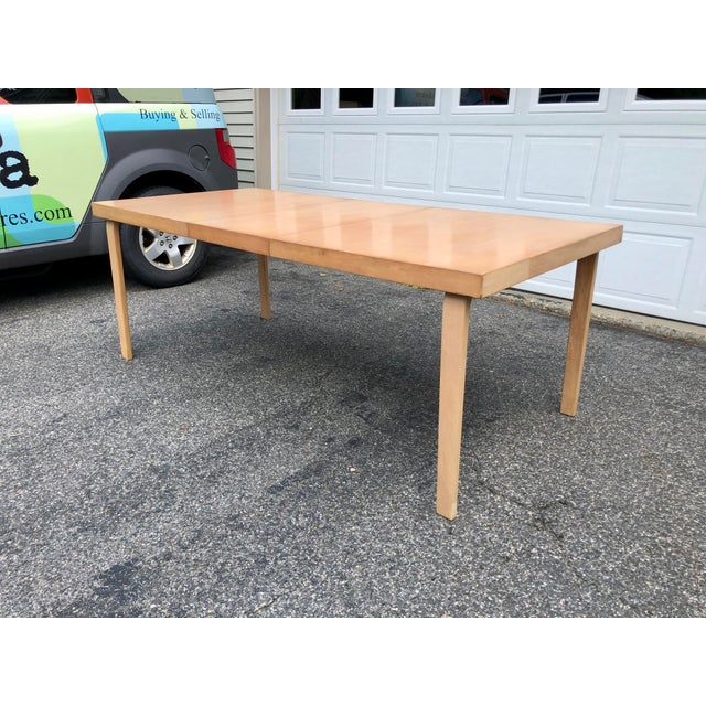 An early rectangular extension dining table with a laminated birch top and solid bentwood legs designed by famed Finnish...