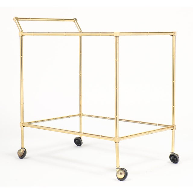 Circa 1950, an elegant rectangular mid-century vintage French brass faux bamboo bar cart or trolley by Maison Baguès. This...