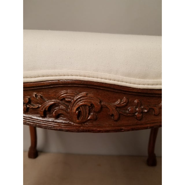 Stylish and graceful, this walnut bench has nice carvings and hooved feet. Newly upholstered in ivory canvas. Please refer...