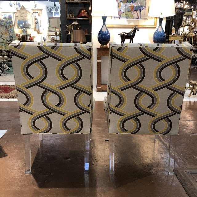 Modern upholstered chairs on acrylic legs - a pair.
