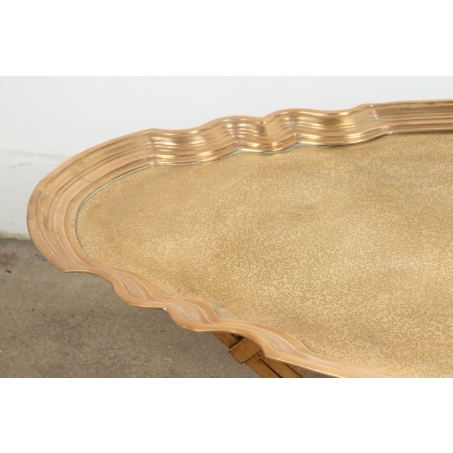 Mid-20th Century heavyweight oval brass tray on an gilt iron stand. This Hollywood Regency style coffee table could be use...