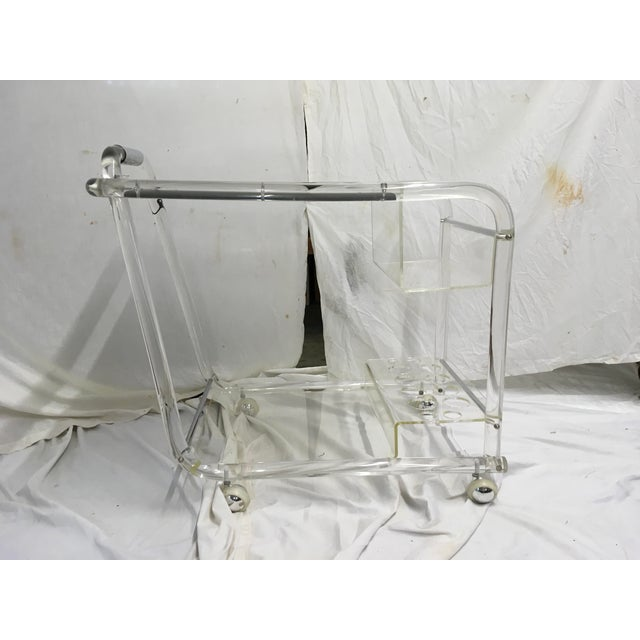 Unusual acrylic bar cart w/ chrome trim. New mirrored top, with top spirits caddy and bottom bar ware caddy. In very good...