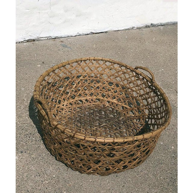 This oversize rattan basket would serve well as storage for larger textiles like blankets and throw pillows. It is unique...