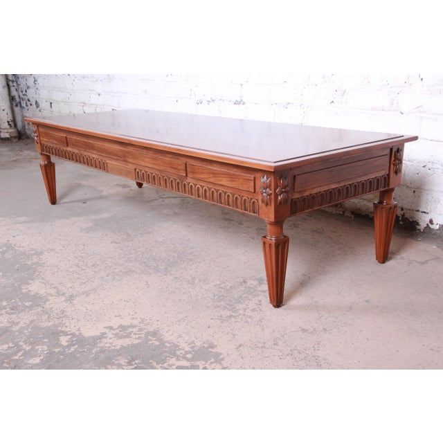 An exceptional French Regency Louis XVI style coffee table by Baker Furniture. The table features stunning burled walnut...