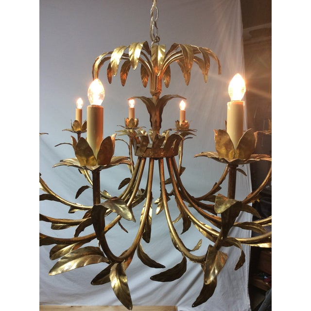"A stunning large twelve-light gilt metal chandelier composed of thin leaves in a palm style. Marked ""Made in Italy"" and..."