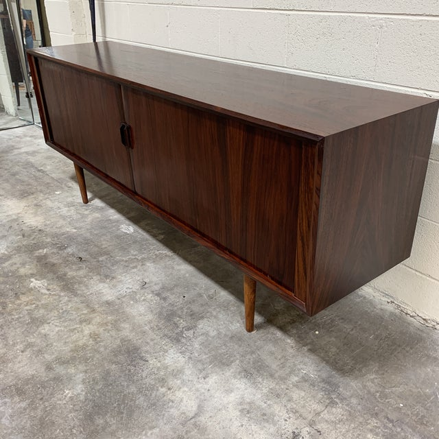 Beautiful mid century rosewood credenza with tambour doors. Doors slide open to reveal 4 center drawers for flatware or...