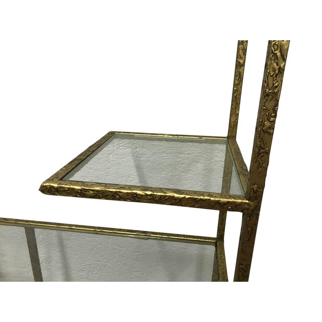 Mid Century Modern etagere with glass shelving and textured gilded finish.