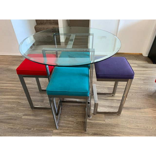 """Fun 42""""h high-top glass table with 4 high bar stools that match. Suede seat cushions in fun bright colors. Frames are..."""