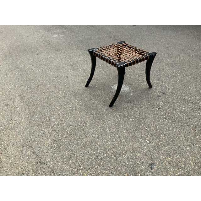 Modern Klismos style ottoman . Ottoman has a dark expresso finish with round leather cording. The Otto is in like new...